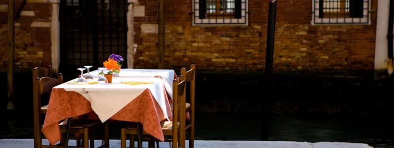 Venice-restaurant table set along the edge of a canal, landscape color photo