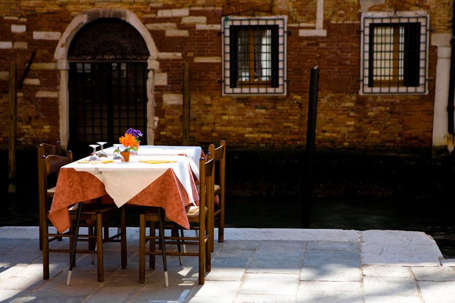 Venice-restaurant table set along the edge of a canal, landscape color photo