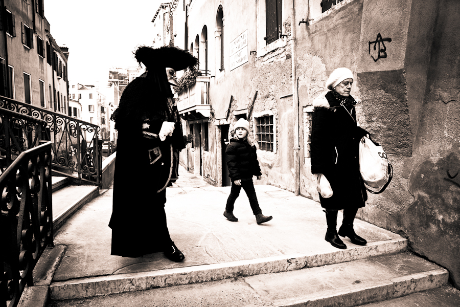 Venice - Little girl staring at man in carnival costume, black and white landscape photo