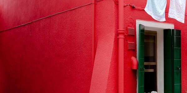 Venice - red colorful house in Burano island, color portrait photo