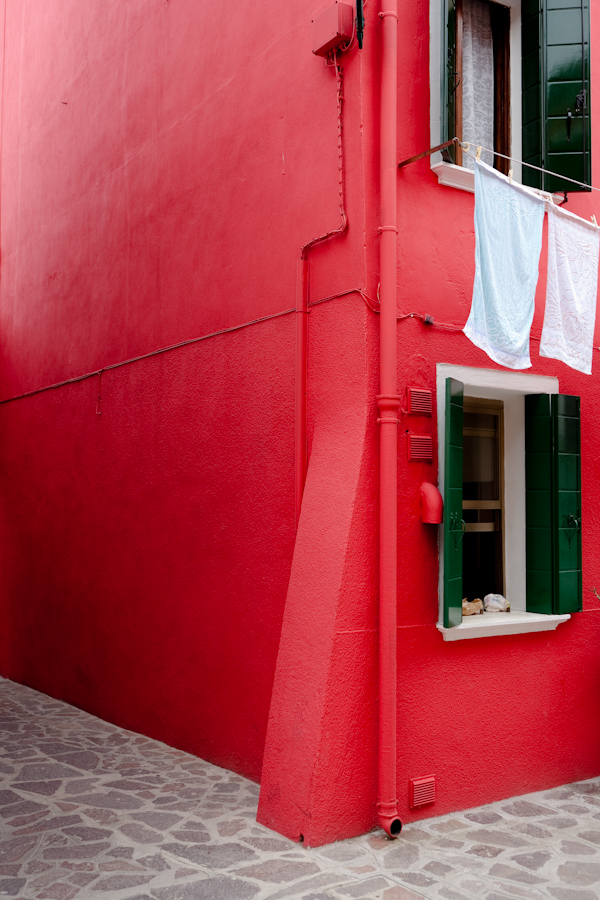 Venice - red colorful house in Burano island, color portrait photo
