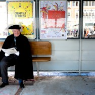 Venice - Venetian resident in carnival costume waiting for waterbus, color landscape photo