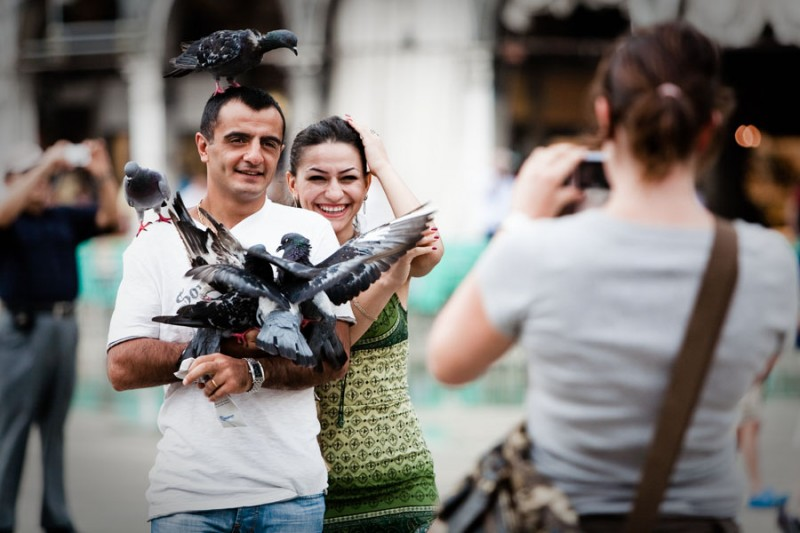 Venice - tourists photographed with pigeons in St. Mark's square, color landscape photo