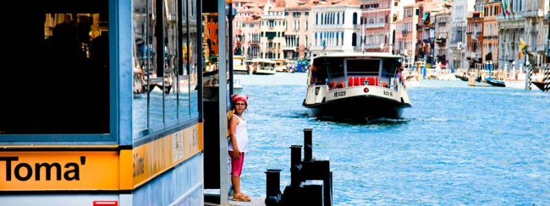 Venice - little girl waiting for the waterbus in Grand Canal, color landscape photo