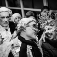 Venice - couple in carnival costumes onboard a waterbus, black and white landscape picture