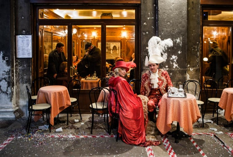 Venice - couple in carnival costumes at a cafè in St. Mark's square